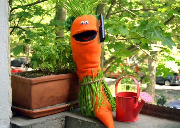Ohrrübe sitzt neben einer kleinen Gießkanne und einer Basilikumpflanze und telefoniert